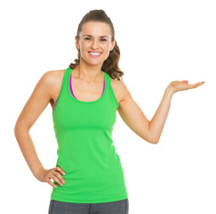 Smiling fitness young woman presenting something on empty palm