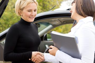 Saleslady congratulating a new car owner