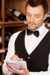 Confident sommelier. Thoughtful young sommelier writing somethin