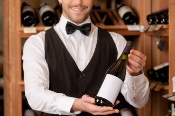 Confident sommelier. Cropped image of cheerful young sommelier h