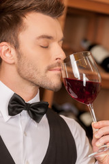 Confident sommelier. Side view of confident young sommelier hold