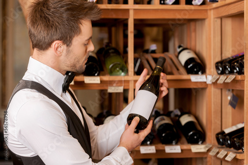 Confident sommelier. Thoughtful young sommelier holding a wine b
