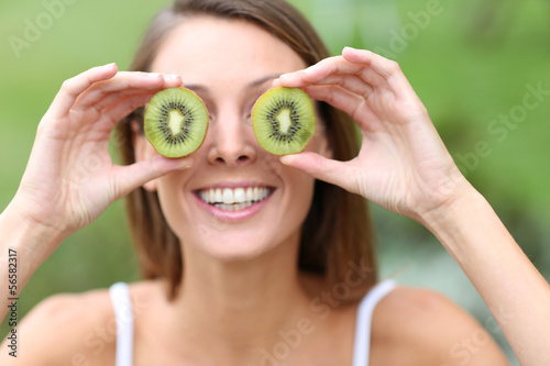 Cheerful girl showing kiwi slices