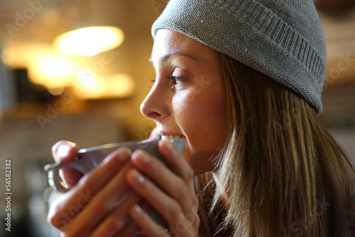 Trendy girl at home having hot drink