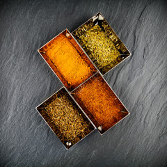 Quatre épices dans des ramequins sur ardoise grise