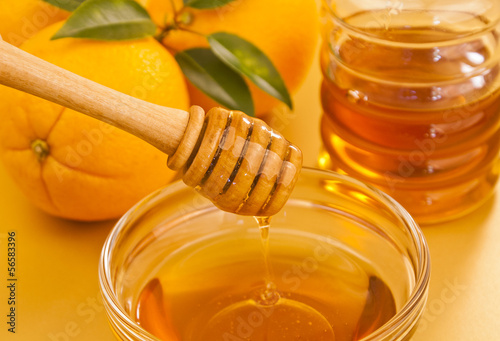 Bowl of honey with wooden dipper drizzler and oranges
