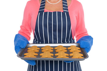 Close up of a woman holding freshly baked gingerbread men