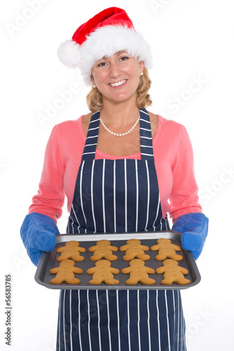 Woman in Santa hat holding a tray of gingerbread men