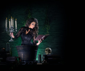 A young and sexy witch making a deadly potion during Halloween