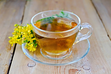 Herbal tea from tutsan in a glass cup on a board
