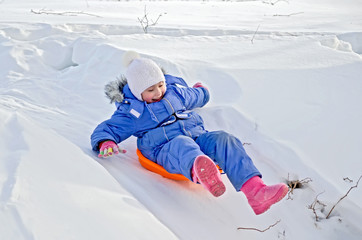 Little girl on a sled sliding on snow