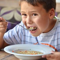 Junge isst Nudelsuppe