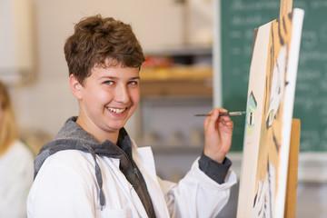 Schüler malt an der Staffelei