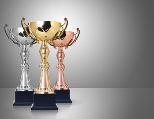 Three trophies, gold, silver and bronze on gray background