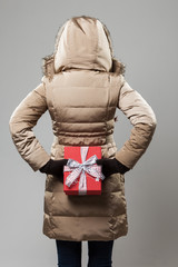 Woman with a Christmas gift behind her back