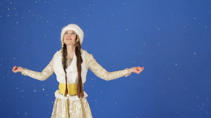 Beautiful snow maiden catching snowflakes