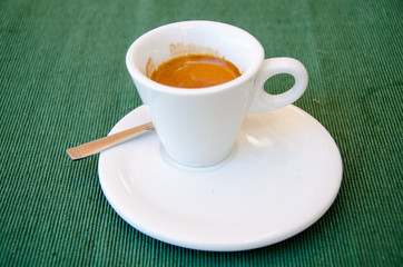 White espresso cup standing on the green textile tablecloth
