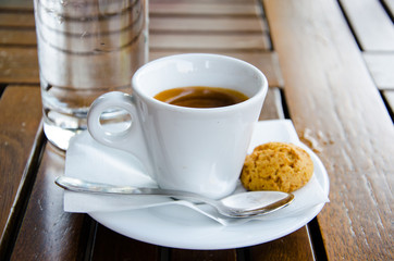White espresso cup, biscuit and glass of water