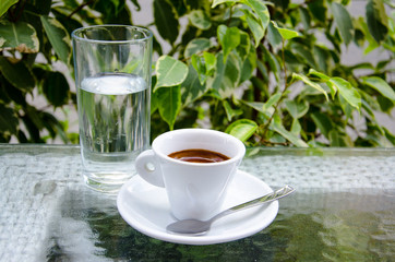 White espresso cup with glass of cold water