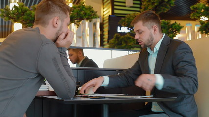 Two men sit at a table and work out a business plan