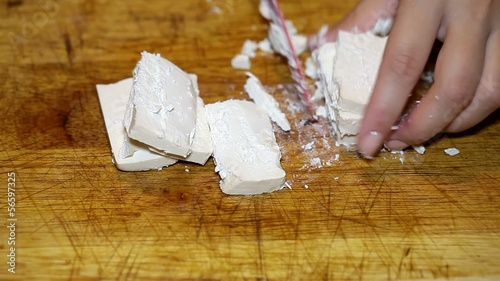 Cutting cheese on wooden plate closeup