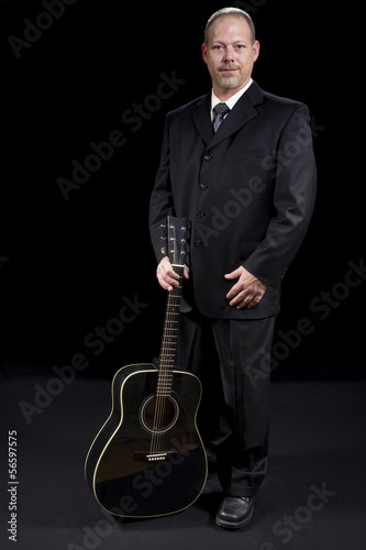 business man in suit standing with guitar on black background