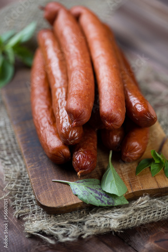 Vertical shot of smoked sausages with basil leaves, close-up