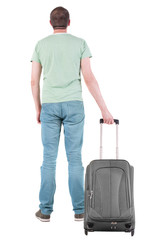 Back view of man with suitcase looking up