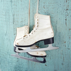 Ice skates on blue vintage wooden background