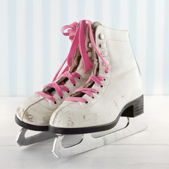 Old ice skates on white and blue vintage background