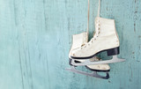Women's ice skates hanging on blue wooden background - 56600741