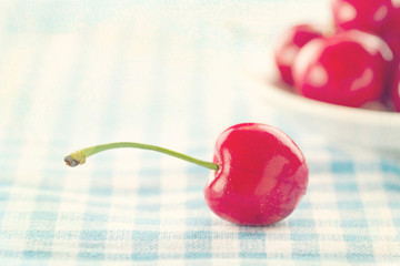 Red cherries on shabby chic blue background