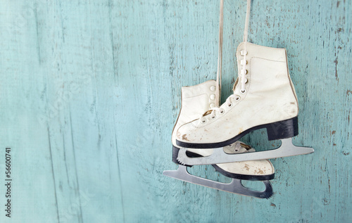 Fotobehang Wintersporten Women's ice skates hanging on blue wooden background