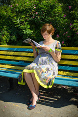 Pregnant woman reading magazine on the bench
