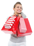 Happy young woman in sweater with christmas shopping bags