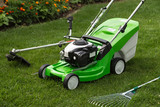 Green lawnmower, weed trimmer, rake and secateurs in the garden