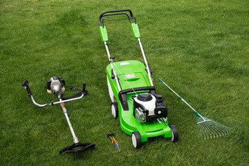 Green lawnmower, weed trimmer, rake and secateurs on the lawn