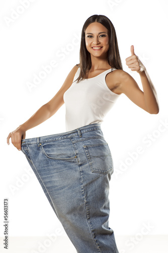 happy attractive girl posing in huge pants with the thumbs up