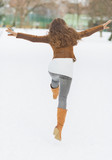 Happy young woman having fun in winter park . rear view