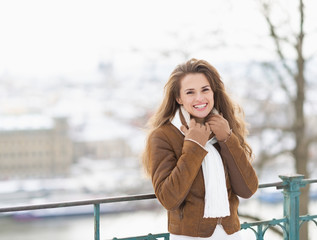 Portrait of smiling young woman in winter jacket outdoors