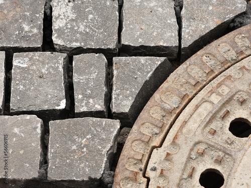 Pflastersteine wurden an einen runden Kanaldeckel angepasst
