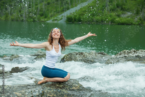Girl drinks clear water from mountain river