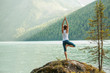 Leinwanddruck Bild - Young woman is practicing yoga at mountain lake