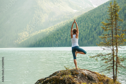 Leinwanddruck Bild Young woman is practicing yoga at mountain lake