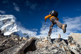 Hiker jumps on the rock near Everest in Nepal