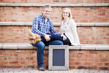 Attractive Caucasian couple sitting next to blackboard