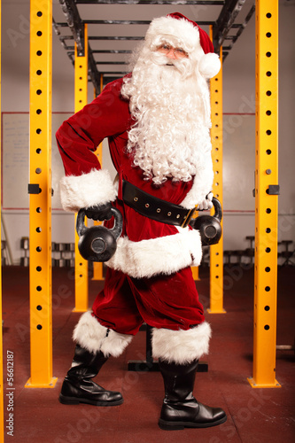 Santa Claus training before Christmas in gym - kettlebells