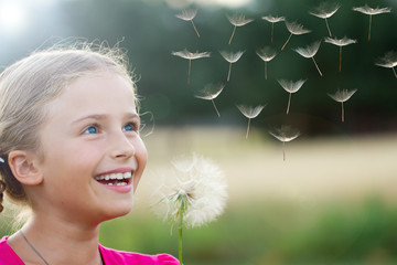 Summer joy - lovely girl blowing dandelion
