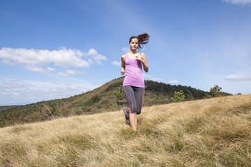 Young woman running outdoors in the nature