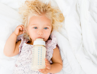 Girl drinking a baby bottle